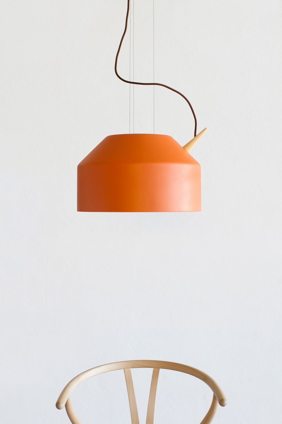 Designerska lampa wisząca Reeno w kolorze pomarańczowym.